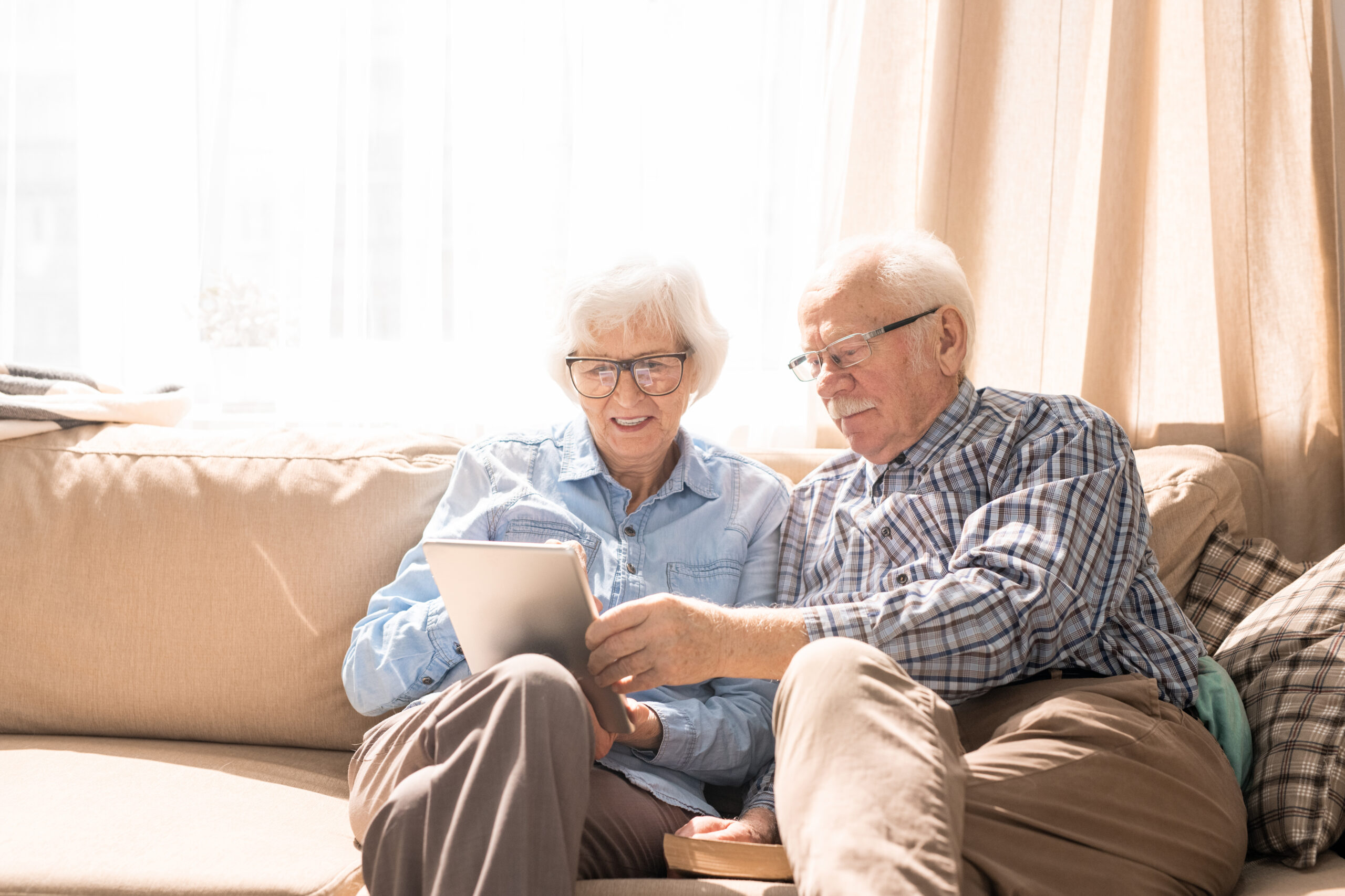 Portrait of modern senior couple using digital tablet sitting on couch at home in sunlight copy space